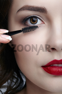 Close up portrait of beautiful young brunette woman face. Female applying mascara to eyelashes