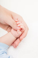 Mother holding newborn baby child little hand with small fingers