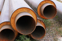 Steel water pipes with PVC isolation shell in stack on ground in construction site