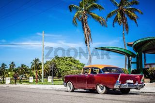HDR - Amerikanischer roter Oldtimer parkt am Strand unter Palmen in Varadero Cuba