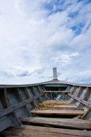 Nose of empty wooden boat on the sky background