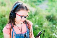 Teen girl listening to music with her headphones outdoor