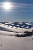 Winter landscape with  heels under snow with Sun on blue sky