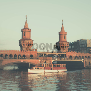 Oberbaumbruecke / Oberbaum Bridge and boat on river Spree in Berlin, Germany