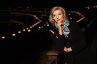 Fashion blond woman in black coat in a night city street