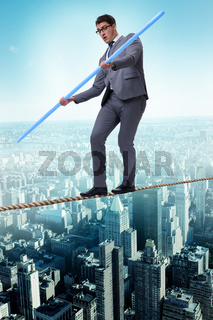 Businessman doing tightrope walking in risk concept
