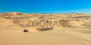 Quad driving in sand desert. ATV in middle of nowhere.