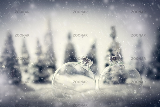 Christmas glass balls in winter miniature forest scenery with snow.