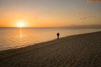 Runner on the beach at sunset