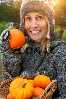 Pretty young woman holding basket of pumpkins