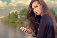 Young woman waiting your call. Dressing in a black wear,  a young caucasian lady is standing by river, holding a mobile phone, with headphones in her ears listening to the music, lost in thought.