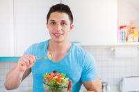 Salat essen junger Mann isst in der Küche gesunde Ernährung vegan Textfreiraum
