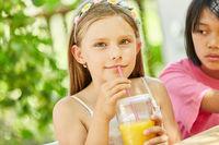 Mädchen trinkt zum Frühstück frischen Orangensaft