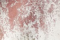 old grungy plastered wall with peeling color
