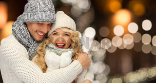 happy couple hugging over christmas lights