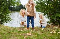 Mutter und Kinder sammeln Blätter