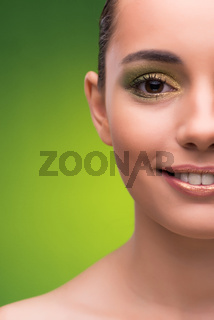 Young woman in beauty concept on green background