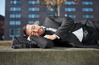 Erschöpfter Geschäftsmann schläft im Freien