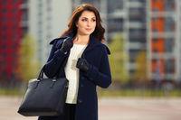 Happy young fashion woman with handbag walking on city street