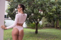 Woman in pink jersey swimsuit and sunglasses in tropical garden