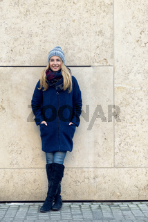 Smiling trendy young woman in winter fashion