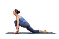 Woman doing Hatha yoga asana Anjaneyasana