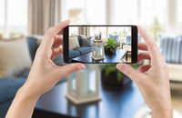 Female Hands Holding Smart Phone Displaying Photo of House Interior Living Room Behind.