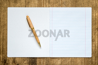 Open lined exercise book with a pen