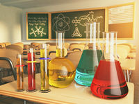 Laboratory glassware with formula on blackdesk in the school chemistry lab.