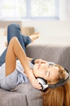 Young woman listening music laying on sofa