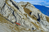 Red railcar of the Pilatus Railway on a steep passage in the Pilatus massif,Alpnachstad, Switzerland