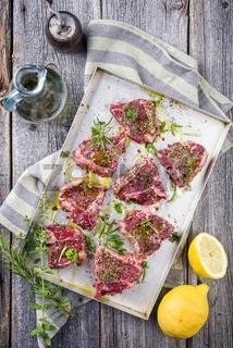 Raw T-Bone Lamb Steak with Seasonings as top view on a metal sheet