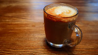 Glass cup of cappuccino on wooden table side view