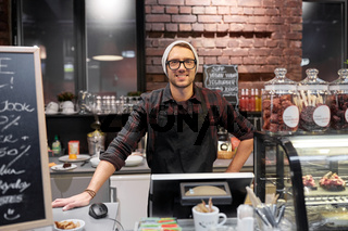 happy seller man or barman at cafe counter