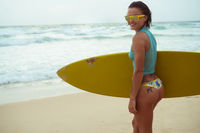 Beautiful woman with yellow surfboard on the beach