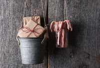 Wrapped Christmas Presents and Candy Canes Hanging against a rustic wood wall.