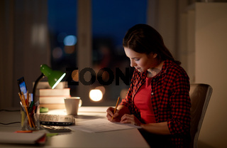 student girl with laptop and notebook at home
