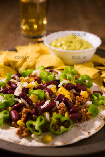 Closeup of Mexican tortillas with meat, red beans, Jalapeno pepper, nachos chips and beer
