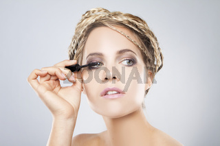 Young beautiful woman with healthy pure skin applying mascara on her lashes