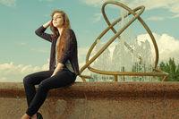 Beautiful teen girl is sitting on granite fountain. Urban outdoors, teenager#39;s street lifestyle. Toned image.