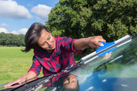 Young woman cleaning car windshield in nature