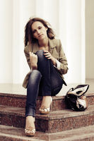 Young fashion woman with handbag sitting on the steps