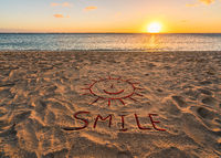 handwritten smile on sand beach