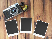 Retro camera, empty photo frames pictures and film canisterrs  on wood table.