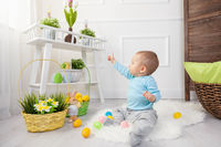 Easter egg hunt. Adorable child playing with colorful Easter eggs at home