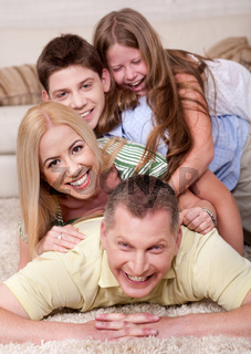Portrait of happy family Lying On Top Of Each Other In living room