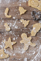 Holiday Cookie shapes on a floured wood kitchen table.
