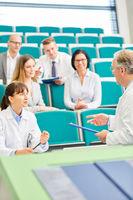 Professor stellt Fragen an junge Ärztin oder Studentin