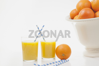 Zwei Gläser Orangensaft, eine Orange und ein paar Strohhälme liegen auf einem Tisch.