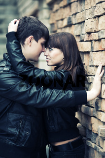 Happy young fashion couple in love at the brick wall